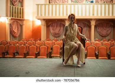 A girl in a vintage style sits in a retro dress on the stage of an empty theater. In the background, an empty auditorium with red chairs