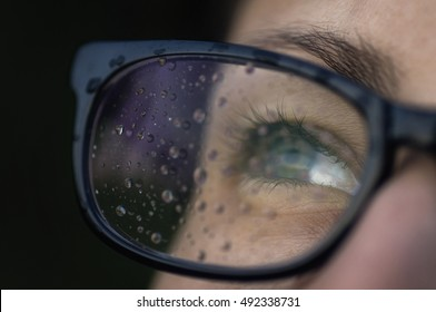 Girl with a vision problem, looks through the glasses. Glasses covered with drops of water (rain).