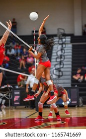 Girl volleyball player spiking the ball during a volleyball game
