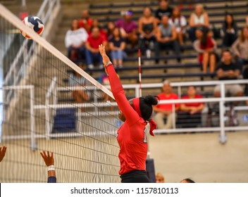 Girl Volleyball players blocking a spike at the net
