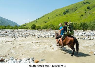 Girl wading dangerous river a on horse, Adischala river, Adishi, Svaneti, Caucasus mountains,Georgia