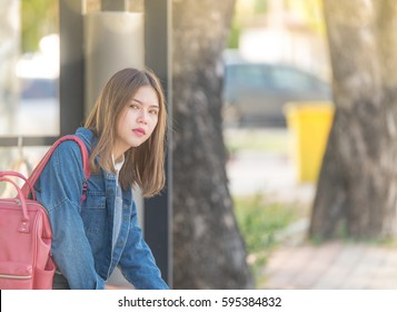 Girl wait for a bus.Bored teen waiting for parents outdoor on the metal bench sitting alone thinking and hoping expressing dissatisfied emotions