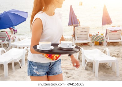 Girl waiter carrying coffee on the beach. Woman serving drinks. Sea and beach sunbeds on the background. Summer vacation at the sea