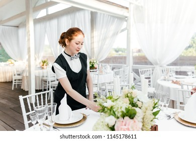 Girl waiter serves Cutlery on the table in the restaurant