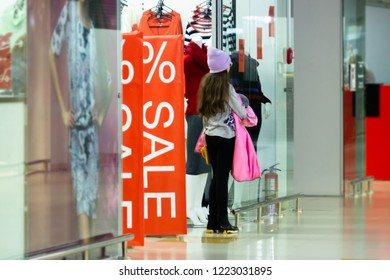 The girl is waiting for parents at the entrance to the store with discounts. Parents have lost track of time. Favorable discount deals.