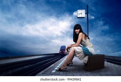 Girl waiting train on the platform of railway station