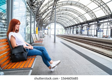 Girl waiting for train at station sitting on bench