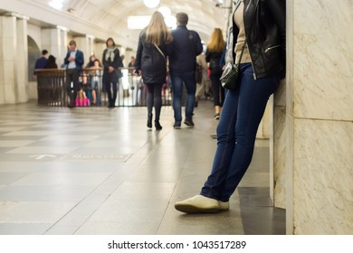 A girl is waiting for a young man in the lobby of the metro station