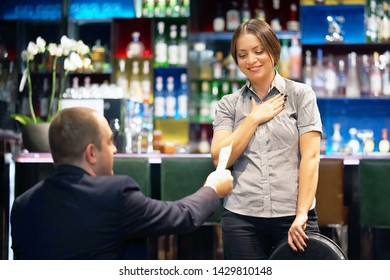 A girl waitre gets a tip from the client in the bar of the hotel. The girl in the vow. Emotions. The concept of service.
