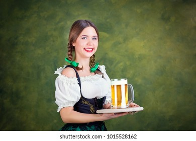Girl waitress oktoberfest in national costume with a mug of beer