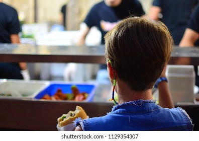A girl waits for lunch at the cafeteria