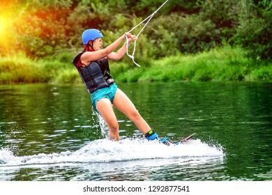 Girl wakeboarding on river lake sea on summer spring day in jacket