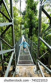 Girl walking above rain forest on canopy tour in Costa Rica