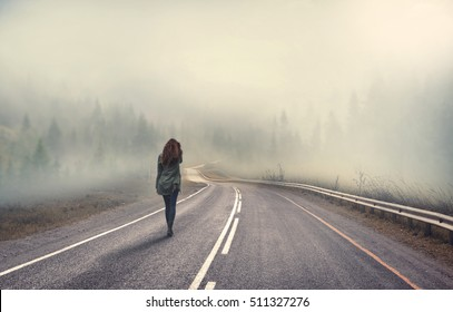 girl walking alone on mountain highway in winter foggy day