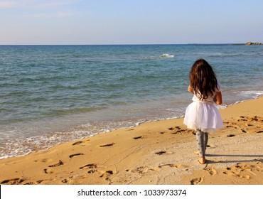 girl is walking along the beach