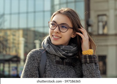 Girl is walking around the city. She has a good mood and she smiles. A student is wearing a coat and a scarf around her neck, the girl is wearing glasses.