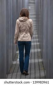 Girl walking away through grey corridor