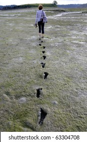 Girl walking barefoot trough mudflat in Brittany, France