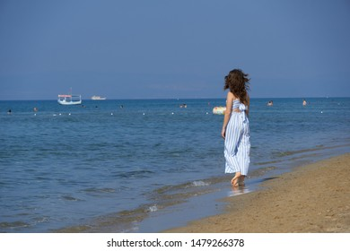 Girl is walking at the beach. Seaside landscape photo was taken in Sarimsaklik Beach, Ayvalik, Balikesir, Turkey