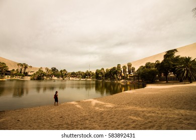 Girl walking and contemplating the lake on oasis in  Huacachina, Ica, Peru.