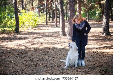 A girl is walking with a dog in the park