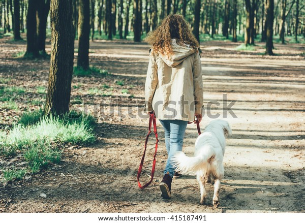 girl walking dog in park