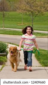 Girl Walking Down the Sidewalk With Dog
