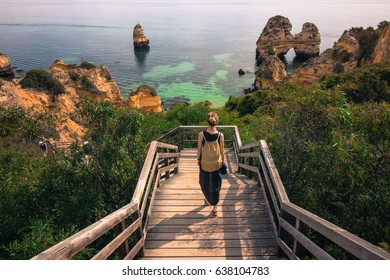 Girl walking down the stairs on Camilo beach in Lagos, Algarve