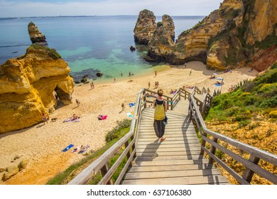 Girl walking down the stairs towards the Camilo beach