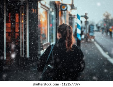 girl walking down the street of the city, falling snow