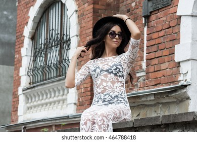 girl walking down the street in a transparent white dress