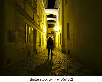 Girl walking empty dark alley during night.