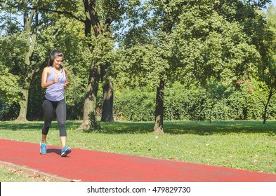 Girl walking fast on the track running and listening to music