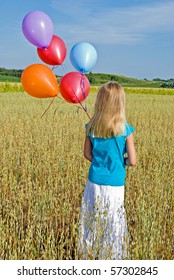 girl walking in field with balloons