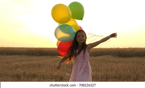 girl walking in a field with balloons.
