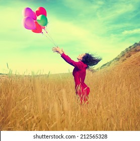 a girl walking in a field letting go of a bunch of balloons done with a vintage retro instagram filter effect