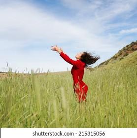 a girl walking in a field letting go