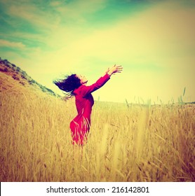 a girl walking in a field letting go of something toned with a retro vintage instagram filter effect