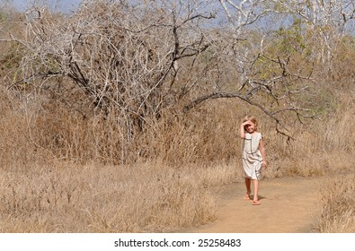 A girl is walking the galapagos forest, looking around for the rare birds
