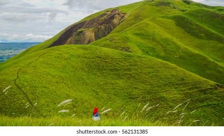 A girl walking happily on a hill at the Samosir Island, near the famous Lake Toba, Medan, Indonesia