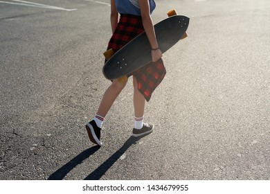 Girl walking holding long board lots of copy space, hipster woman with longboard