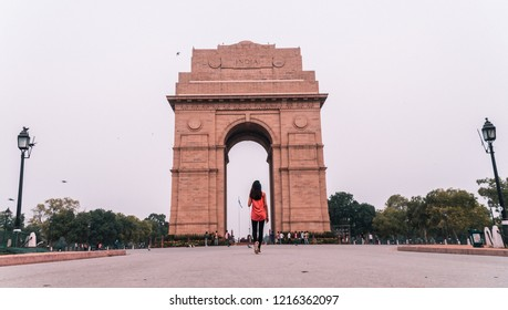 Girl walking up to India Gate at sunrise