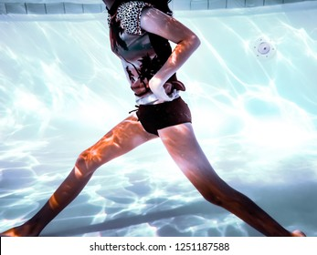 Girl walking with a long stride underwater.