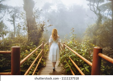 Girl walking in magic forest national park in white dress