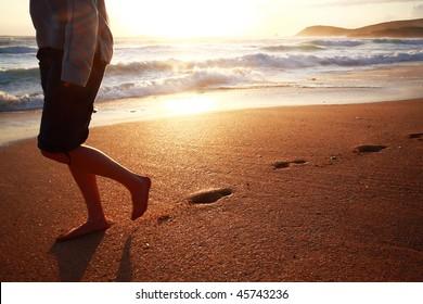 A girl walking on a beach in Cornwall