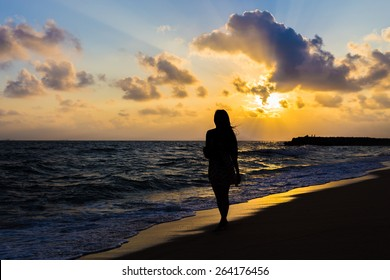 Girl walking on beautiful foggy beach at sunrise silhouette style