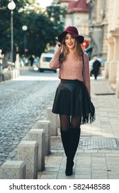 Girl walking on busy cubic stone street of old town during the day at noon. Trendy dressed young woman matching feminine outfit with black knee high boots, walking like on cat-walk.