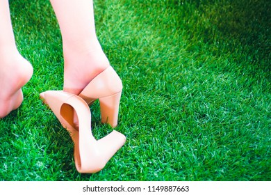 Girl is walking on the grass, losing one shoe. Shoes in beige on the grass, sunny day. Copy space for text.