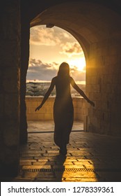Girl walking on a medieval door of a castle. Beautiful view of the sunset