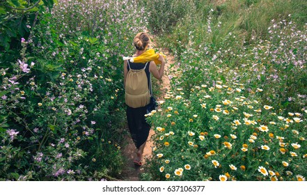 Girl walking on a path filled with flowers towards the beach in Lagos